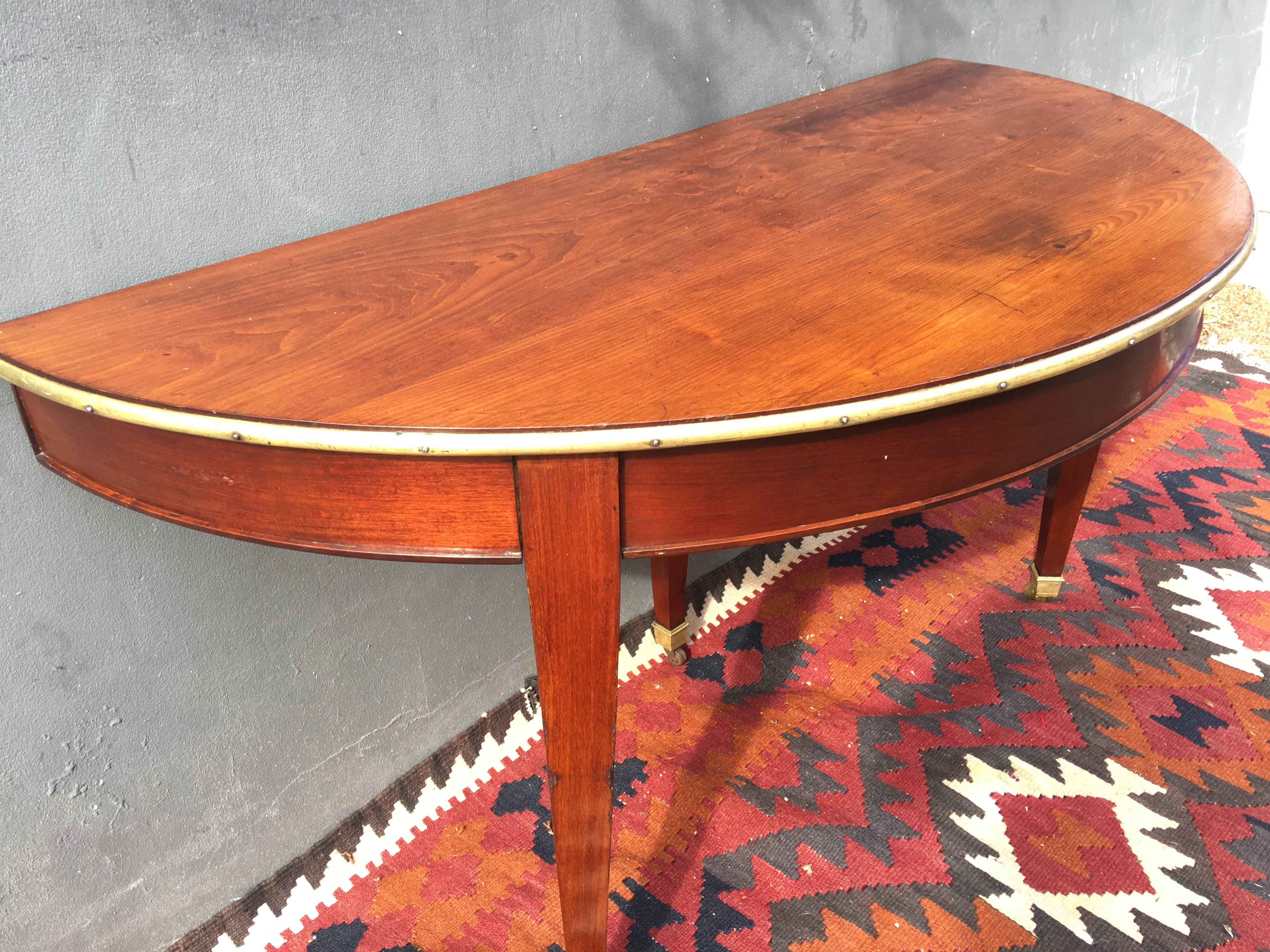 Ideal Pair of French Demi Lune Tables Lovely pair of mid century Empire side tables with warm faded mahogany and brass bound tops on tapered legs capped by brass